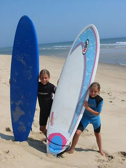 Two children holding surfboards on the beach at the Cape Cod National Seashore